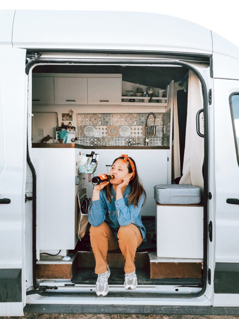 Woman Drinking Beer After Long Day In Her Van