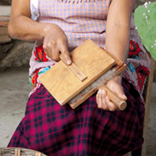 Brushing (carding) sheep's wool to make Mexican rugs from Oaxaca